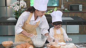Beautiful woman and cute little Asian boy with eyeglasses, chef hat and apron playing and baking bakery in home kitchen funny. Hom. Emade food and bread stock video footage