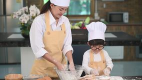 Beautiful woman and cute little Asian boy with eyeglasses, chef hat and apron playing and baking bakery in home kitchen funny. Hom. Emade food and bread stock footage