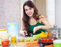 Beautiful woman cuts green celery Royalty Free Stock Photography