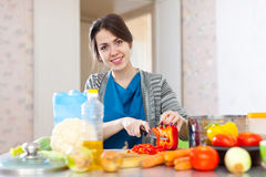 Beautiful woman cuts red pepper Royalty Free Stock Photos