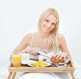 Beautiful woman cutting croissant Royalty Free Stock Photography