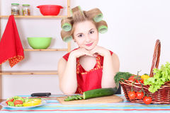 Beautiful woman cutting cucumber in the kitchen Royalty Free Stock Photos