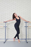 Beautiful woman dancer posing near barre in ballet studio. Stock Photo