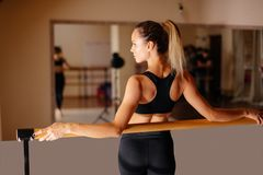 Woman dancer posing near barre in ballet studio. Beautiful woman dancer posing near barre in ballet studio Royalty Free Stock Images