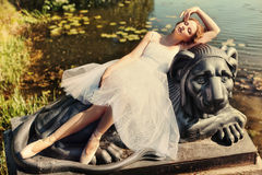 Beautiful woman dancer resting on the lion statue. Girl dancer resting on the nature of a lion statue Royalty Free Stock Photo