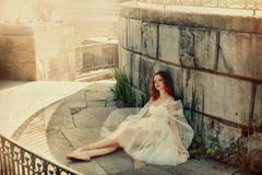 Beautiful woman dancer resting in the shade of a stone building. Fairy woman dancer resting in the shade of a stone building Royalty Free Stock Image