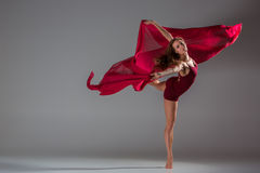 Beautiful woman dancer wearing maroon swimsuit posing on a grey studio background. Young beautiful woman dancer with long brown hair wearing maroon swimsuit stock image