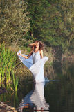 Beautiful woman dances in a lake with white veil Royalty Free Stock Image