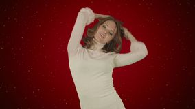 Beautiful woman dances on red background with snow royalty free stock images