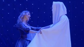 Beautiful woman dances with stranger in coat and mask and singing on the scene. Beautiful woman in long dress sing song on colorful stage in the modern theatre stock footage