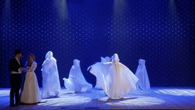 Beautiful woman dances with strangers in cloaks on the stage in theatre. Beautiful woman in long dress sing song on colorful stage in the modern theatre. People stock video footage