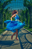 Beautiful woman dancing barefoot in a long blue dress Stock Photography