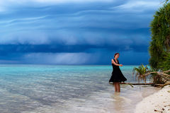 Beautiful woman dancing on the beach with a tropical storm. Beautiful young woman dancing on the beach with a tropical storm Stock Photo