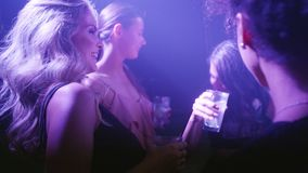 Beautiful woman dancing at disco with friends stock footage