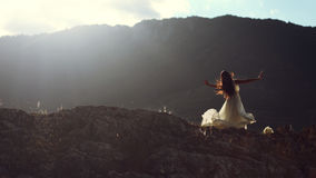 Beautiful woman dancing in evening light. Young beautiful woman bride in long white dress stretching arms spinning and dancing on mountain royalty free stock images