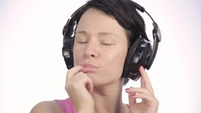 Beautiful woman dancing in headphones while listening to a music on a light background