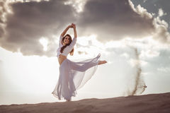 Beautiful woman dancing at sunrise. Beautiful woman dancing on the beach at the sunrise royalty free stock images