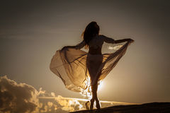 Beautiful woman dancing at sunset. Beautiful woman dancing on the beach at the sunset stock photos