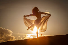 Beautiful woman dancing at sunset. Beautiful woman dancing on the beach at the sunset royalty free stock image