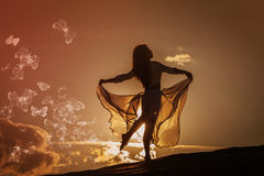 Beautiful woman dancing at sunset. Beautiful woman dancing on the beach at the sunset with butterflies royalty free stock images