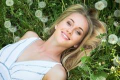 Beautiful woman among dandelions Stock Photo