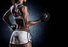 Beautiful woman on a dark background is engaged in fitness Royalty Free Stock Images