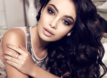 Beautiful woman with dark curly hair and evening makeup Stock Photo