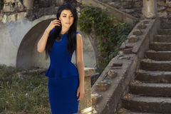 Beautiful woman with dark hair in blue dress stock image