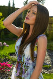 beautiful woman with dark hair and blue eyes at garden Royalty Free Stock Image