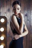 Beautiful woman with dark hair in elegant black dress with bijou. Fashion interior photo of beautiful brunette in elegant black dress posing in dressing room Stock Image