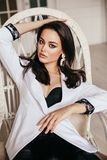 Beautiful woman with dark hair in elegant chic jacket sitti royalty free stock images