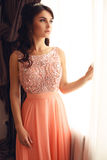 Beautiful woman with dark hair in elegant coral dress with diadem Royalty Free Stock Photography