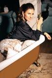 Beautiful woman with dark hair in elegant dress posing near luxury bath. Fashion interior photo of beautiful woman with dark hair in elegant dress posing near royalty free stock photography