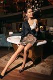 Beautiful woman with dark hair in elegant dress posing near luxury bath. Fashion interior photo of beautiful woman with dark hair in elegant dress posing near stock images