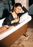 Beautiful woman with dark hair in elegant dress posing near luxury bath. Fashion interior photo of beautiful woman with dark hair in elegant dress posing near royalty free stock images
