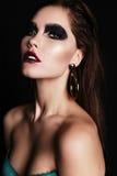 Beautiful woman with dark hair and extravagant black smokey eyes makeup. Fashion studio portrait of beautiful woman with dark hair and extravagant black smokey Stock Photos