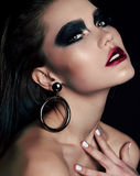 Beautiful woman with dark hair and extravagant black smokey eyes makeup Royalty Free Stock Photography