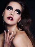 Beautiful woman with dark hair and extravagant black smokey eyes makeup Stock Photos