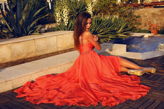 Beautiful woman with dark hair in luxurious red dress posing in park. Fashion outdoor photo of beautiful woman with dark hair in luxurious red dress posing in royalty free stock images