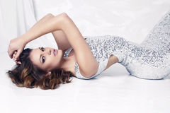 Beautiful woman with dark hair  in luxurious silver dress Stock Photo