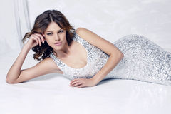 Beautiful woman with dark hair  in luxurious silver dress Stock Images