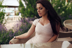 Beautiful woman with dark hair wearing elegant dress,sitting in summer cafe Royalty Free Stock Photography