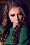 Beautiful woman with dark hair wearing elegant green dress Stock Photos