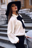 Beautiful woman with dark hair wearing elegant hat and blouse Stock Images