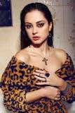 Beautiful woman with dark hair wearing elegant leopard print dress and bijou. Fashion interior photo of beautiful woman with dark hair wearing elegant leopard royalty free stock image
