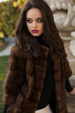 Beautiful woman with dark hair wearing luxurious fur coat Stock Images
