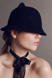 Beautiful woman with dark hair wears elegant black hat and silk bow on neck stock photo