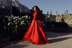 Beautiful woman with dark hair wears luxurious red dress Royalty Free Stock Image
