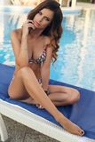 Beautiful woman with dark long hair in swimming suit, relaxing n Stock Image