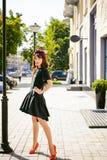 Beautiful woman in a dark stylish dress. Portrait of a fashionable gi
